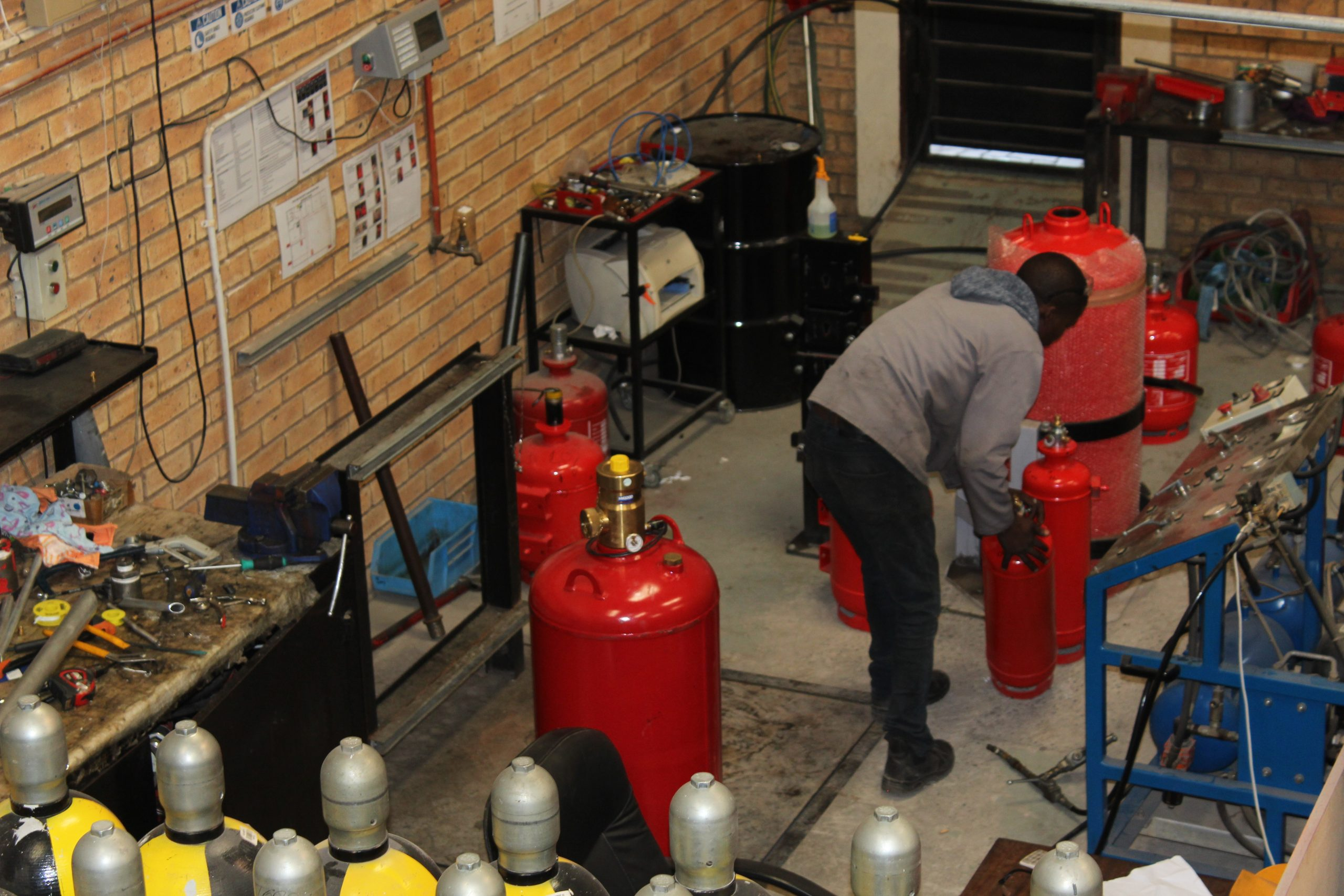 Fire Suppression Equipment Servicing Man Attending To Gas Cylinders